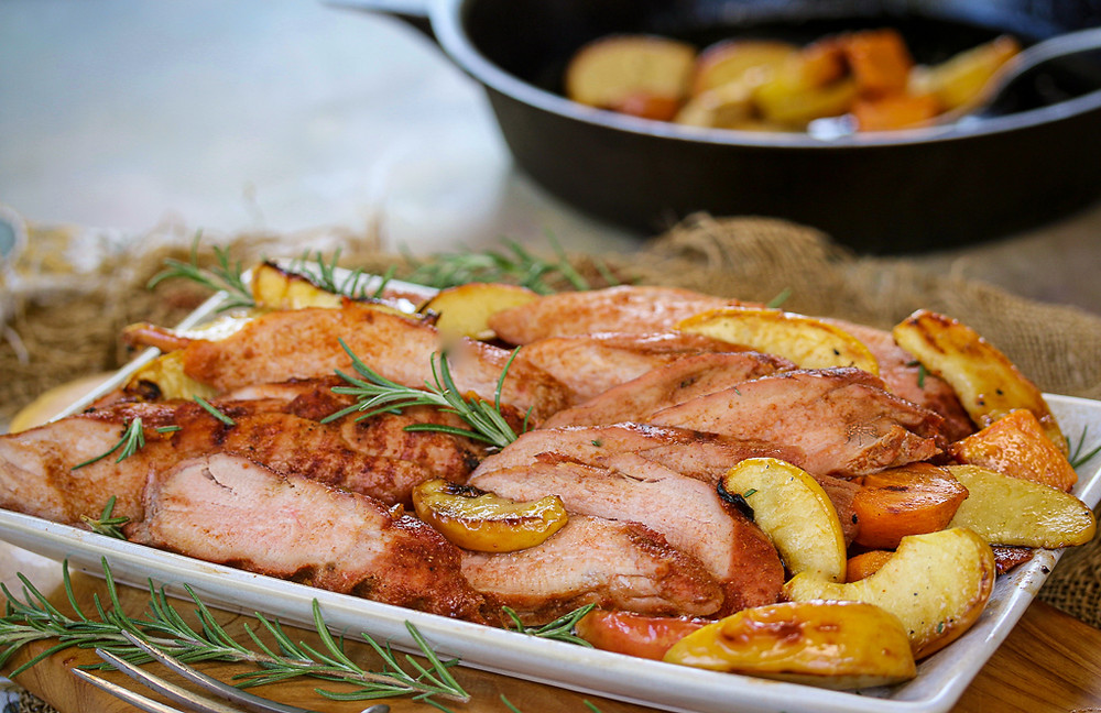 A platter of smoked pork, apples,and persimmons.