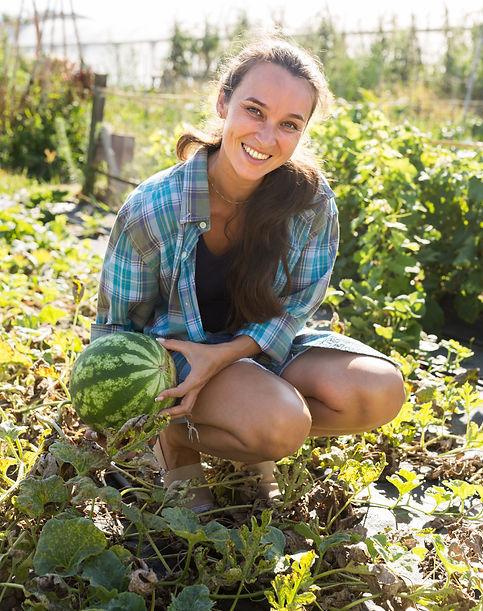 Portrait of smiling female gardener checking watermelon while gardening in garden.jpg
