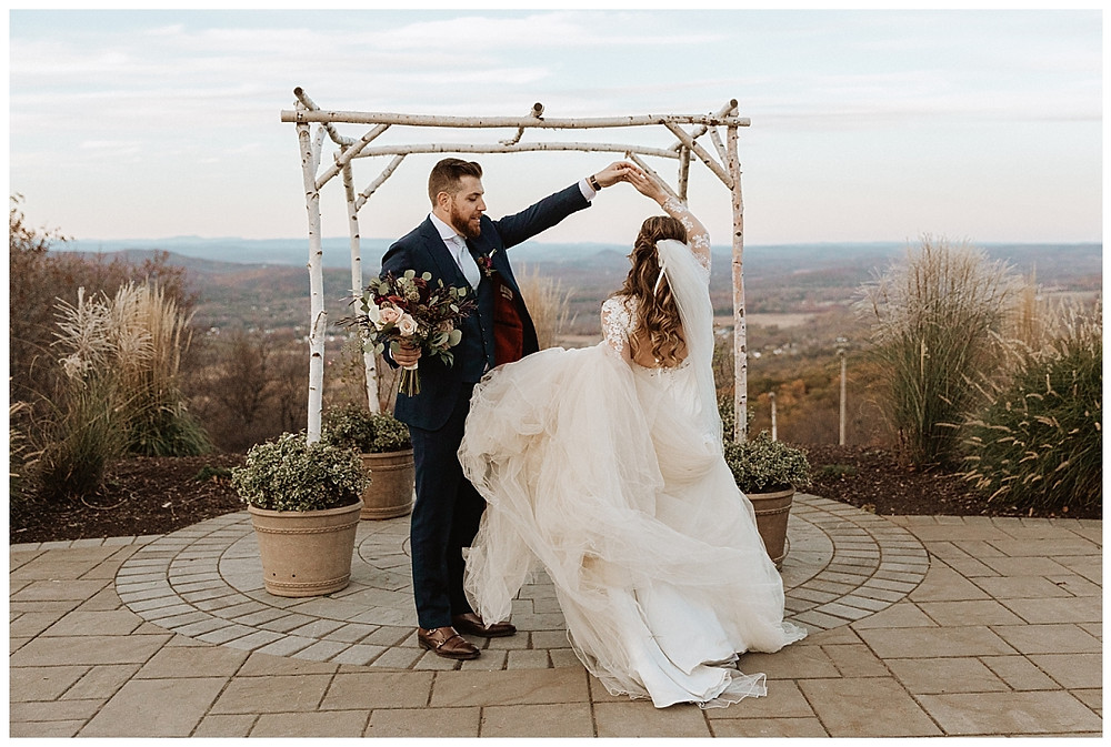 Mountaintop Bride and Groom Portraits in front of Wedding Arch