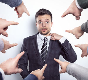 Many fingers pointing at a businessman.j