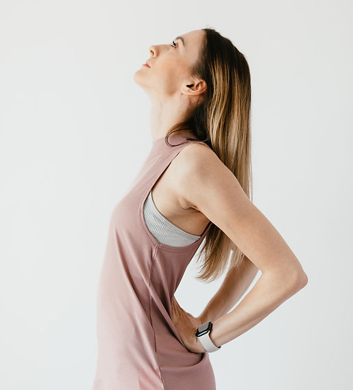 A woman looking upward, bending backward, with her hands on her lower back.