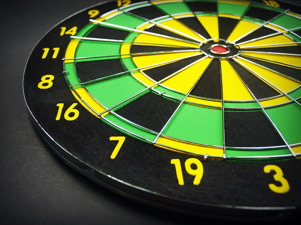 A green and yellow dartboard with a red bullseye laying on a table.