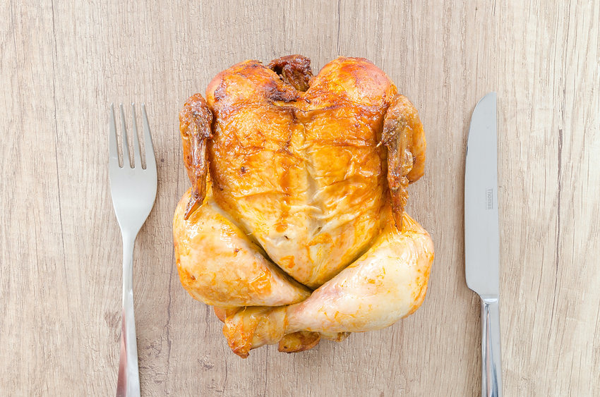 A roasted whole chicken sitting between a fork and a knife.