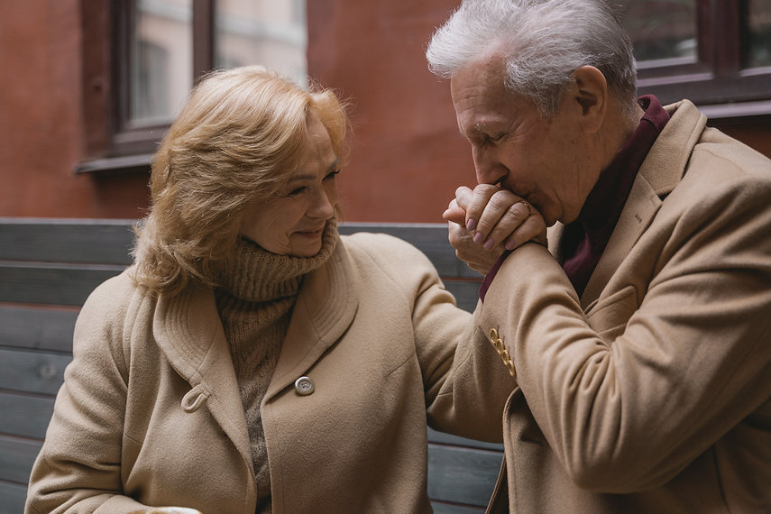 An older couple is holding hands. The man is kissing the woman's hands.