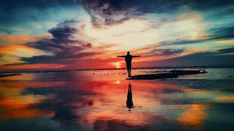A person silhouetted by a pink and blue sunset stands on a rock surrounded by water with arms outstretched in triumph.