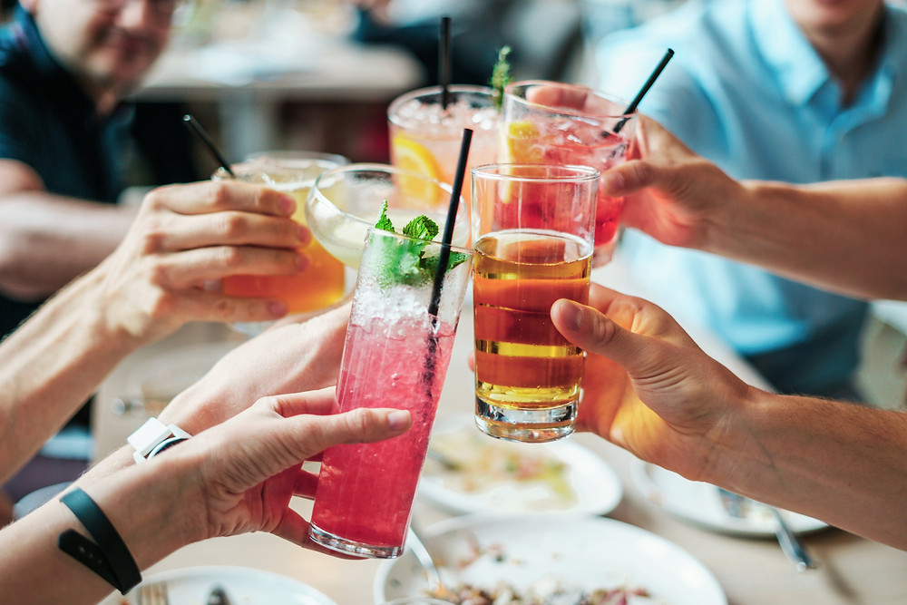 A group of people clinking various drinks as a cheers.