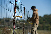Wilmington, North Carolina-Man working on electric fence.