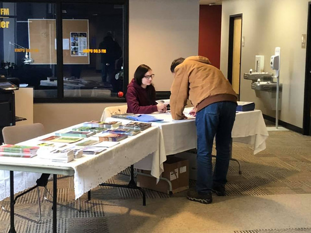 Abby checking in guests at an event for the local watersheds.