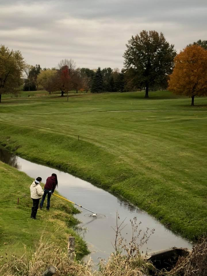 Abby collecting water from Muchakinock Creek at Edumson Park in Oskaloosa.