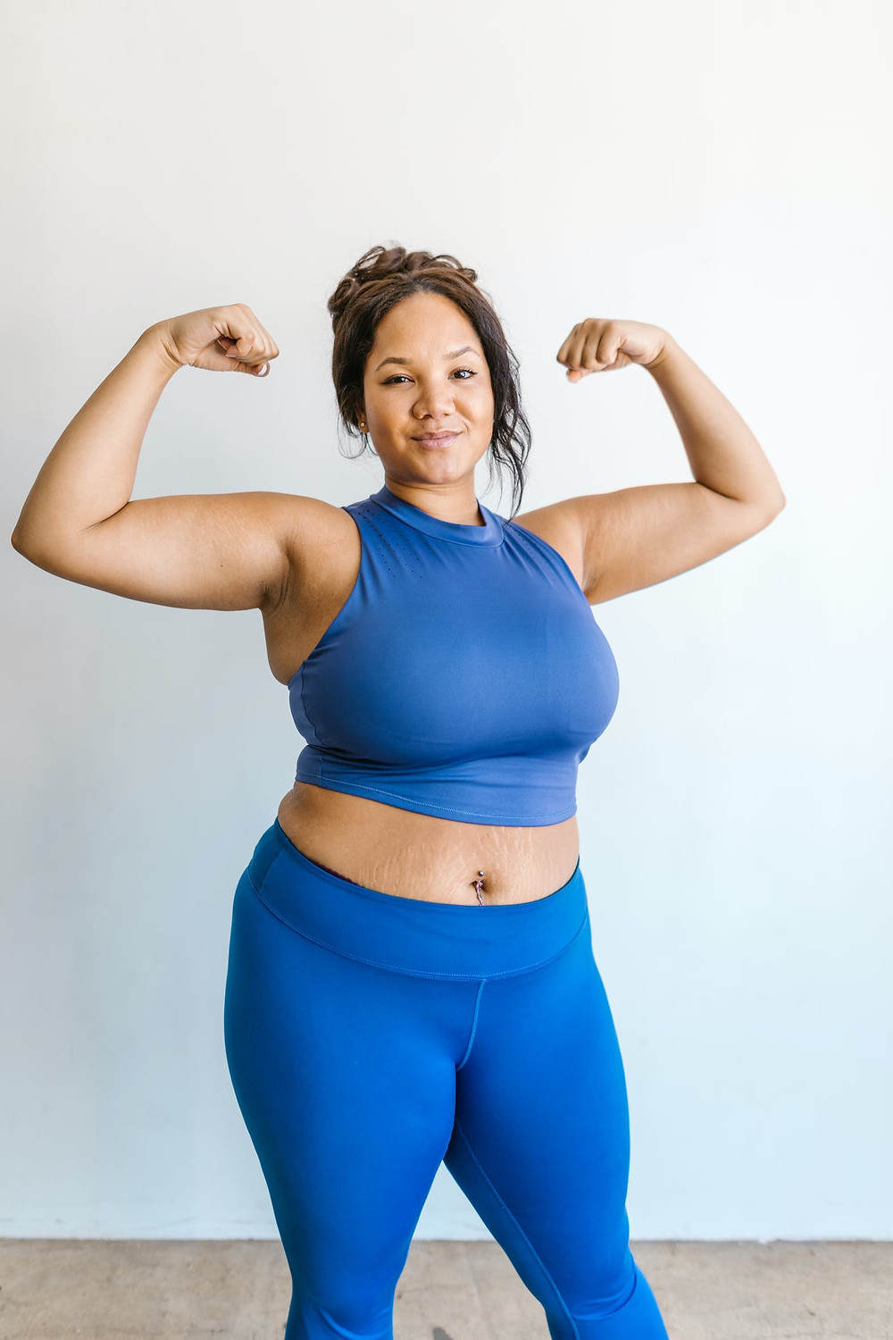 Fat brown mixed race woman in blue athletic crop top and leggings proudly flexing her biceps and smiling