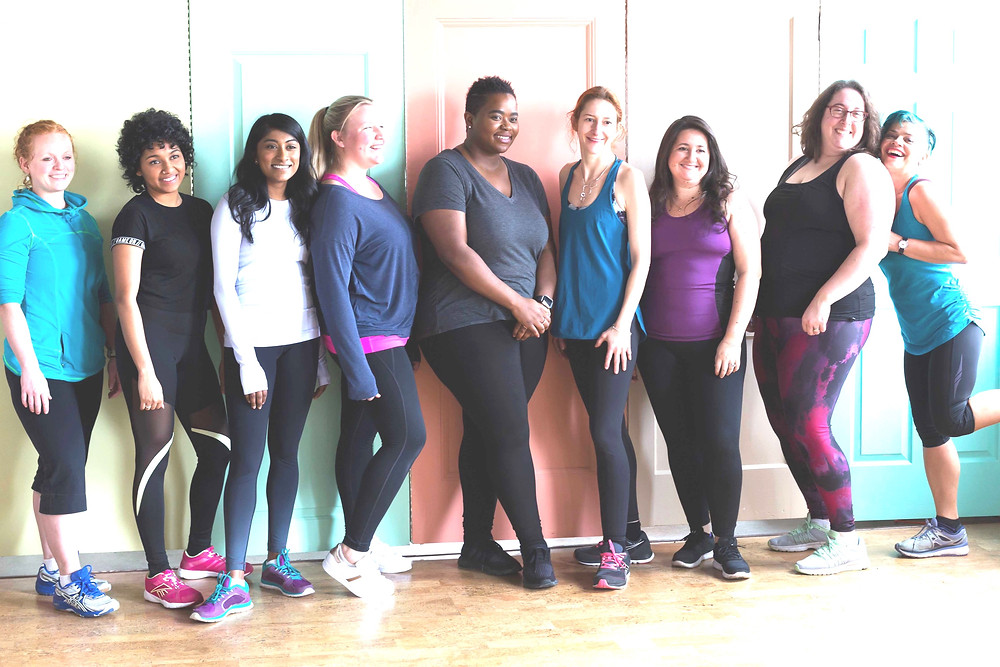 A group of women of different races and diverse body shapes wearing athletic clothes smiling and posing for a photo.