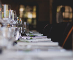 Long dinner table with chairs, table linens, wine glasses, and cutlery.