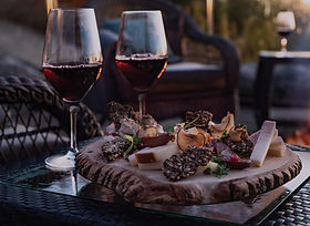 Two red wine-filled glasses with cheese board on outdoor table.