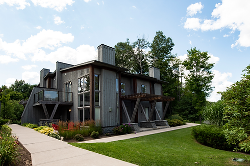 Two-storey grey loft with front garden, Muskoka chairs, and surrounding sidewalks and greenery.