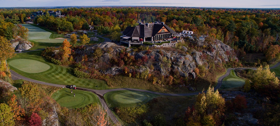 Clifftop clubhouse on rocky landscape with surrounding golf course and forest with fall foliage.