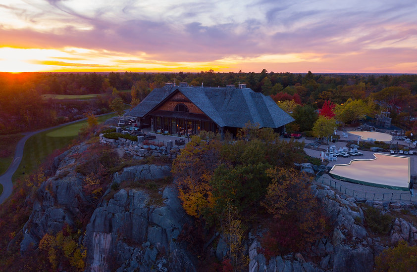 Clifftop clubhouse on rocky landscape with fall foliage, featuring restaurant terrace, infinity pool and swimming pool.