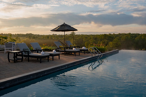 Infinity pool at sunrise with deck, lounge chairs and umbrella in summer.