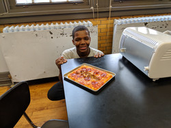 boy with pizza made in cooking club