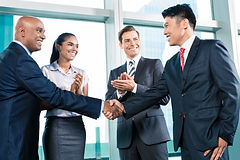 A group shaking hands after a collaboration meeting