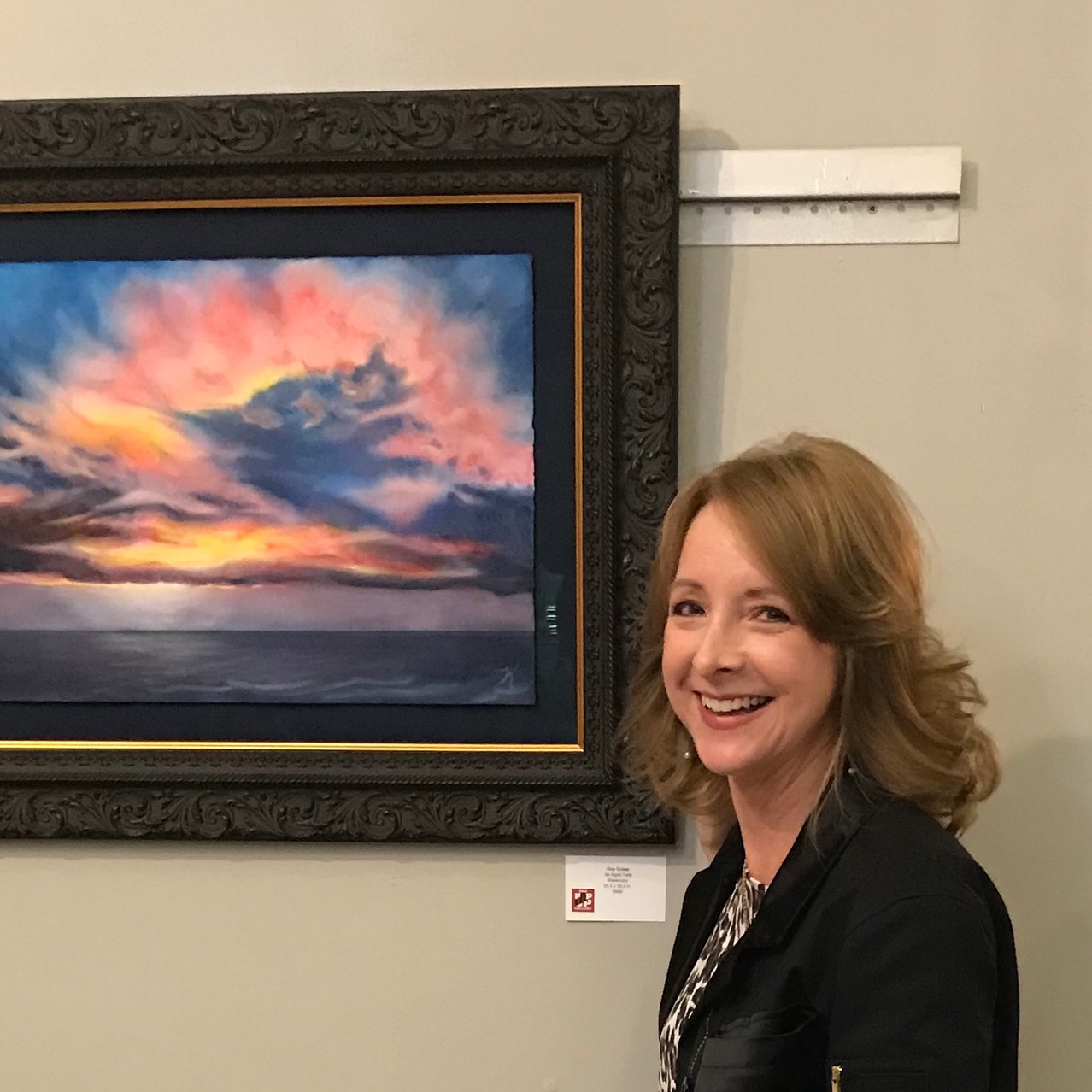 """Artist Kay Cross stands with her watercolor """"As Night Falls"""""""