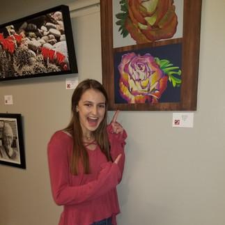 Artist Kaiya Harris stands next to her work.