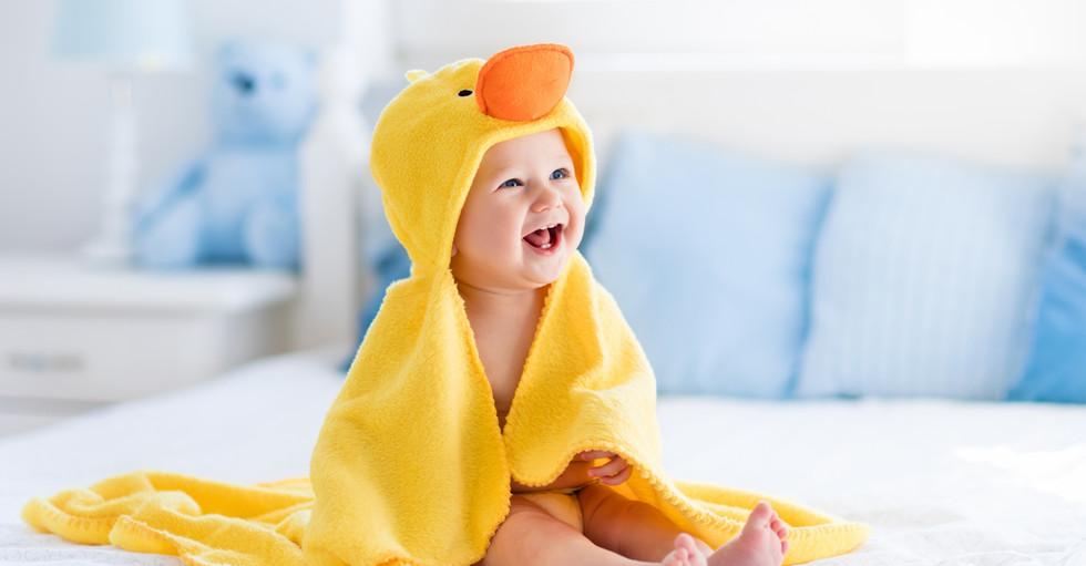 Happy laughing baby wearing yellow hoode