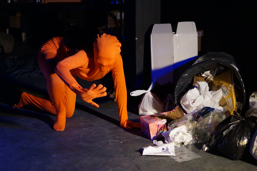 A woman in an orange leotard crouches next to an overturned garbage can full of trash.