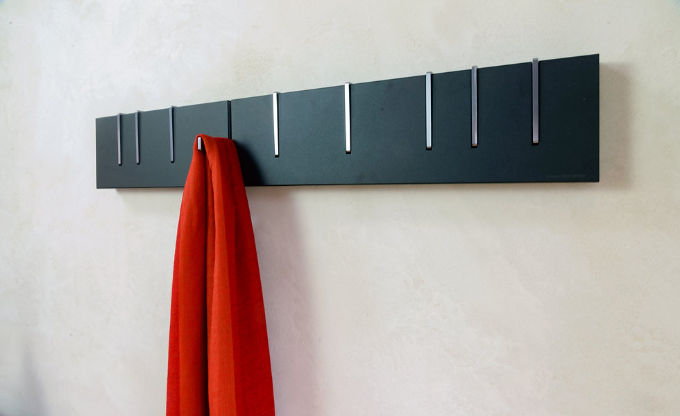 Symbol Coat Rack in NOIR (Black) finish on plaster wall with red scarf hanging from one hook.