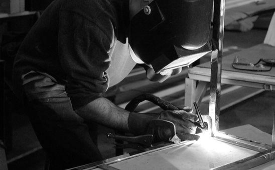 David E. Scott welding a table frame