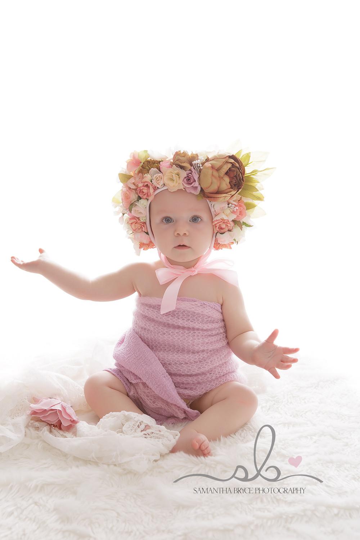 baby girl sitting in a flower bonnet