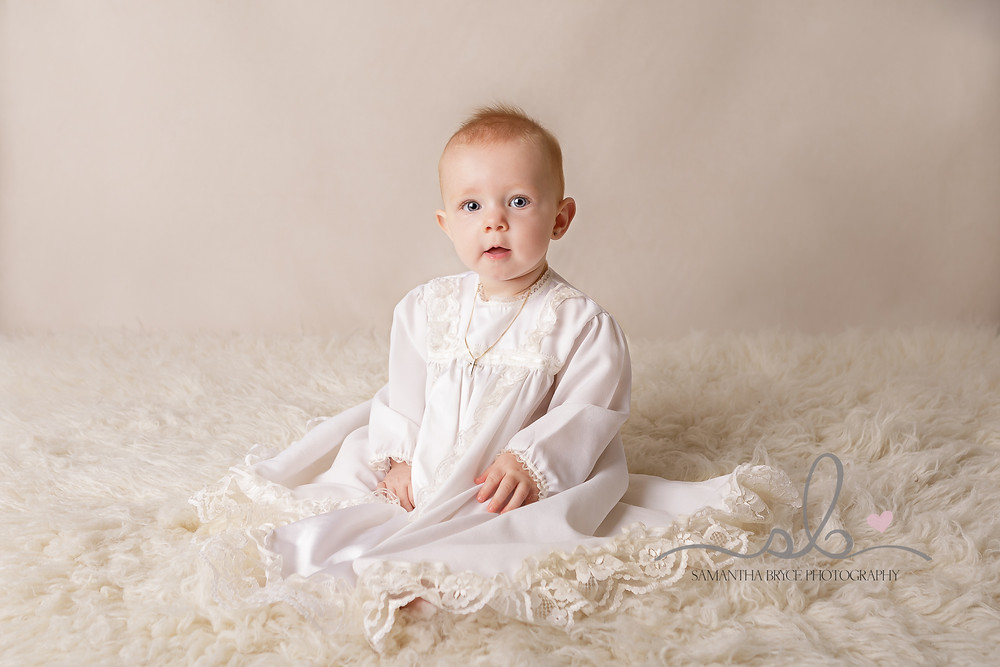 baby girl sitting in her christening gown
