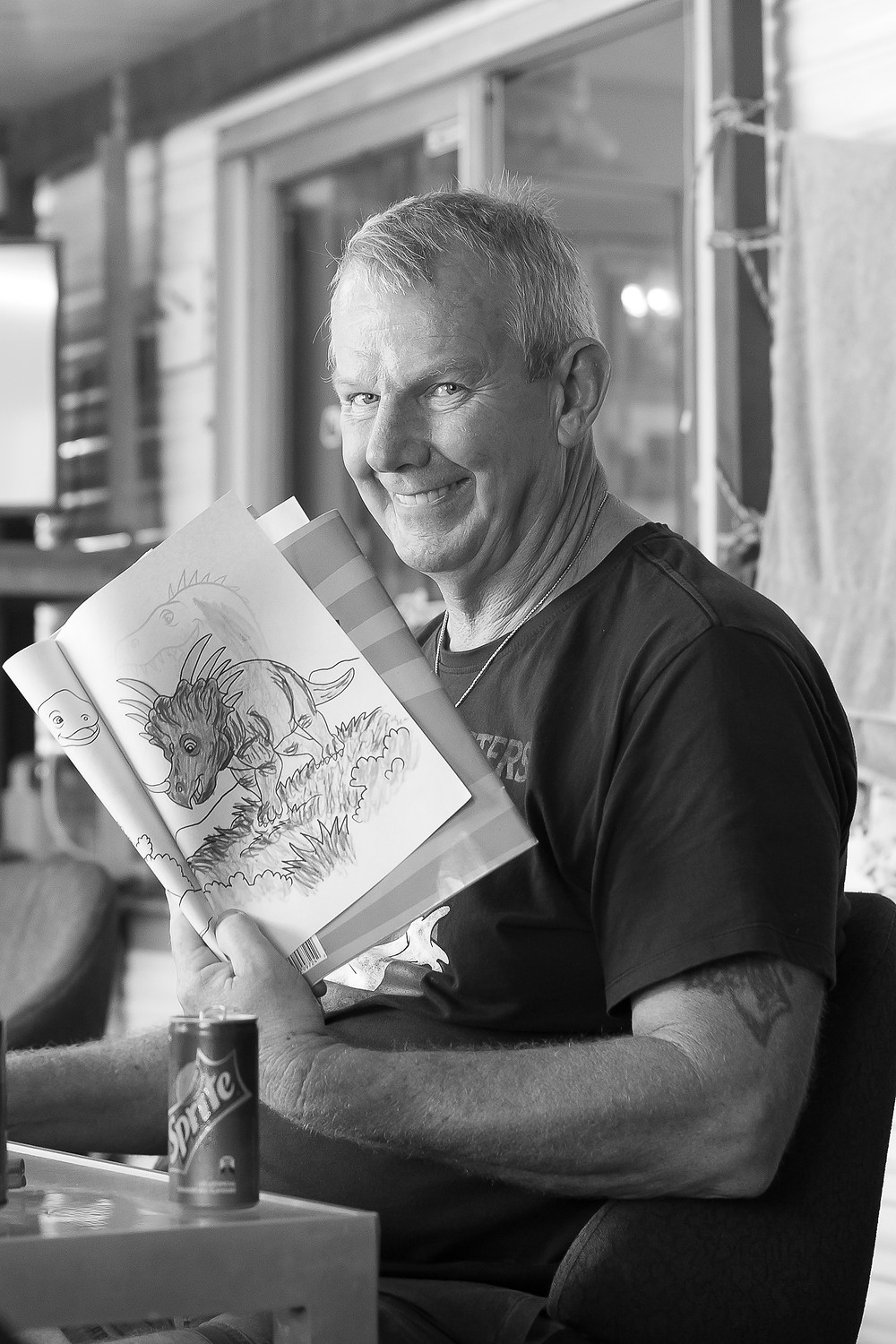 Man holding colouring in book smiling
