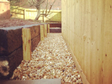 Feather edge fencing, retaining railway sleepers and golden flint