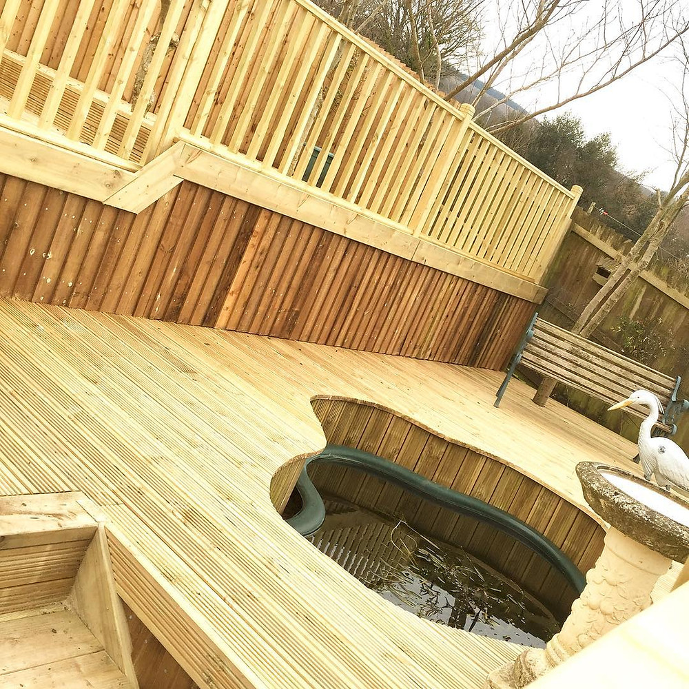 A garden make over where feather edge fecning was built and a multiple level decking with balustrade, steps and feature built around a pond. arkgardenservices.co.uk
