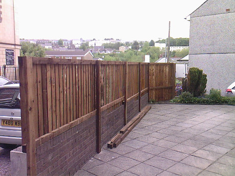 Feather edge fencing on top of a wall