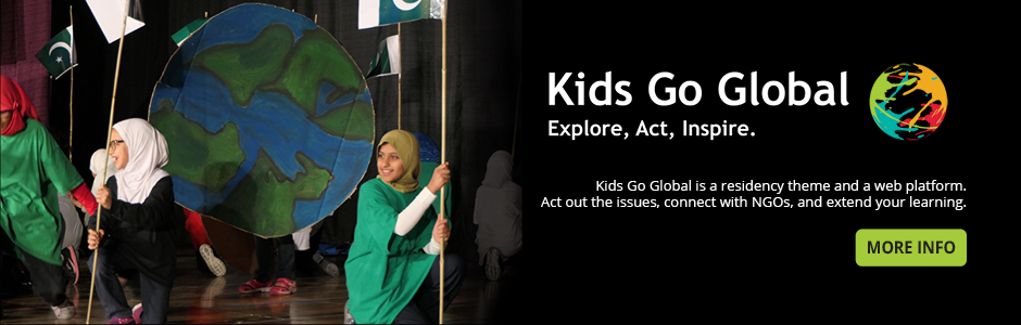Two students in hijabs hold up flags in front of a child-painted cardboard cut out of the earth