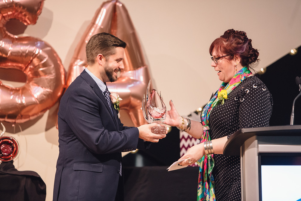 Man handing an award to a happy woman in a polka dot dress