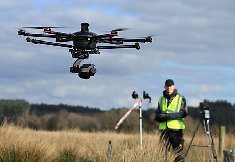 Drone and crewmen doing an aerial inspection of a tower