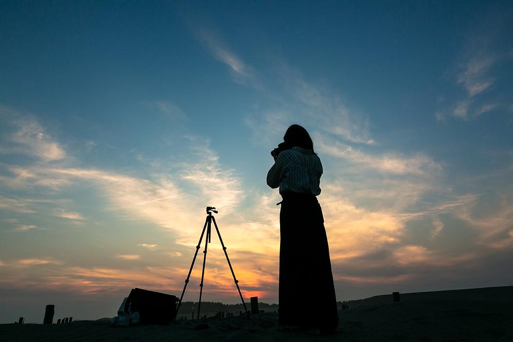 夕日に向かってカメラを構える女性
