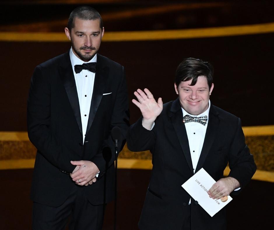 Na imagem o ator Zack Gottsagen acenando para a platéia e segurando um envelope branco na mão esquerda, está ao lado do ator Shia LaBeouf, ambos vestindo terno preto.
