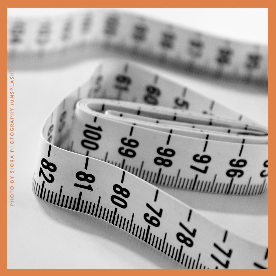 A picture of a black and white measuring tape on a white surface. The photo is by Siora Photography on Unsplash.