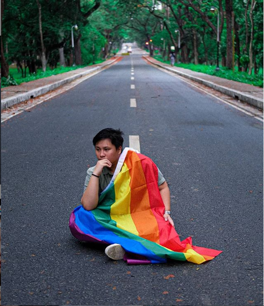 Man sits in front of a carless road with The Gay Agenda's rainbow flag draped over his shoulder.