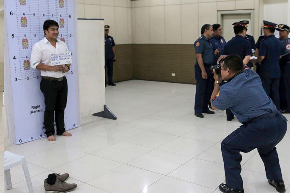 Bong Revilla habang sya ay kinukuhanan ng mug shot.