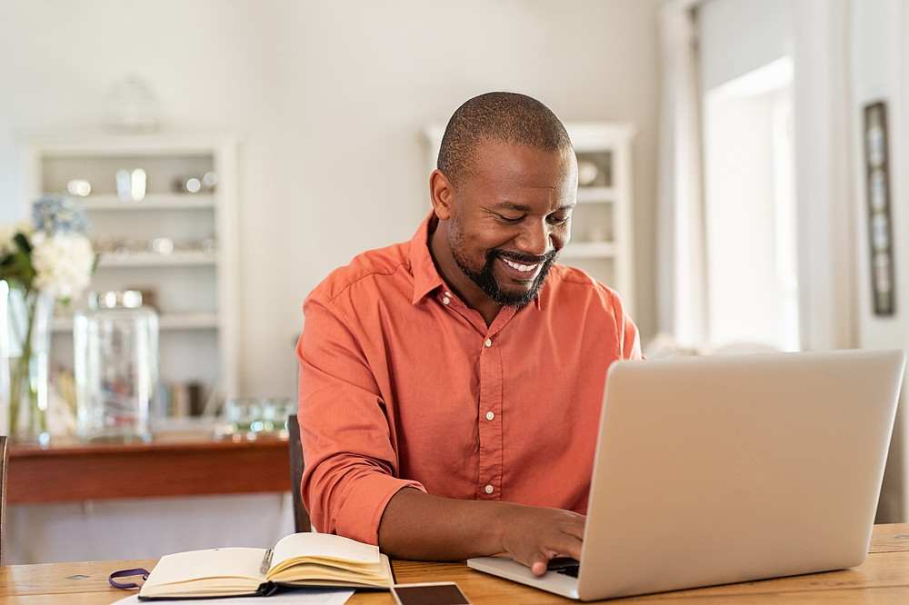 Man on laptop, smiling with a book next to him. He is feeling connected and social in spite of stay at home order in Illinois. Online Therapy in Illinois can help you too!