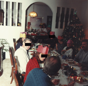 A typical Christmas dinner with Grandma at the far head of the table, sporting her paper crown.