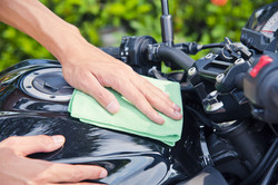 Hand with man cleaning motorcycle with g