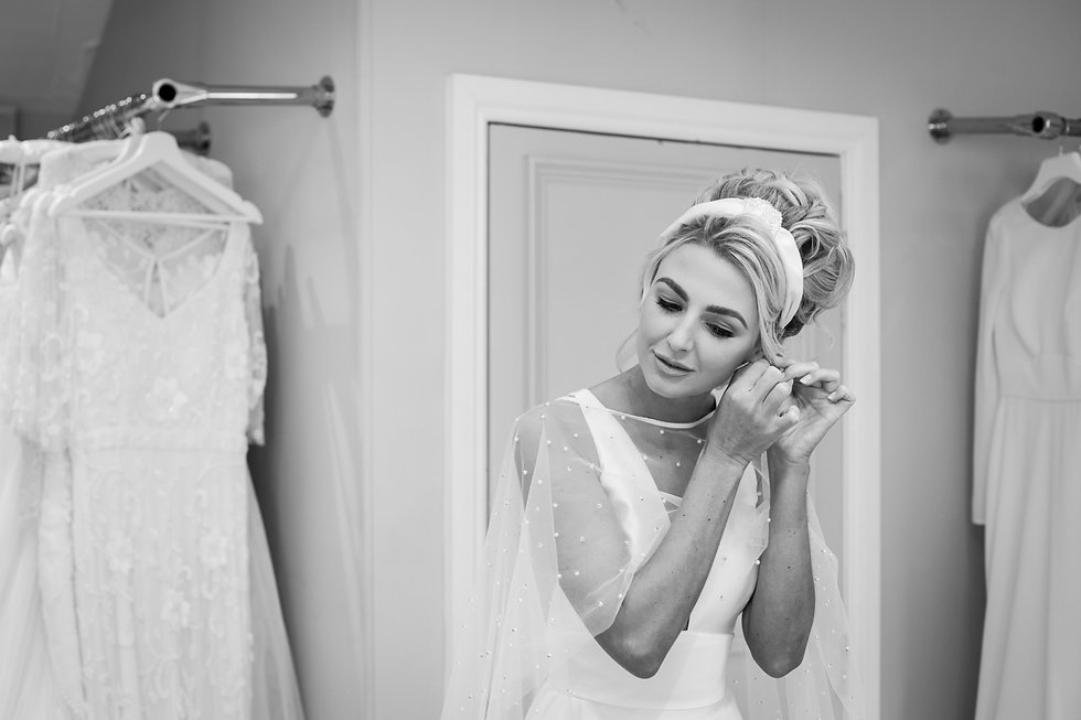 Bride trying on bridal accessories and jewellery wearing Deborah K Design headpiece