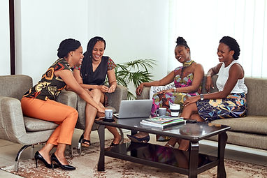 Group of Black women laughing on couch i