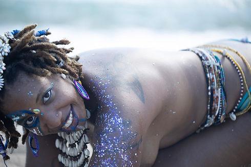 Jaiye Empress lying in sand in waist beads (Photo credit: Jose Lawrence)