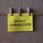photo coming soon text on a yellow sticky note with three clips